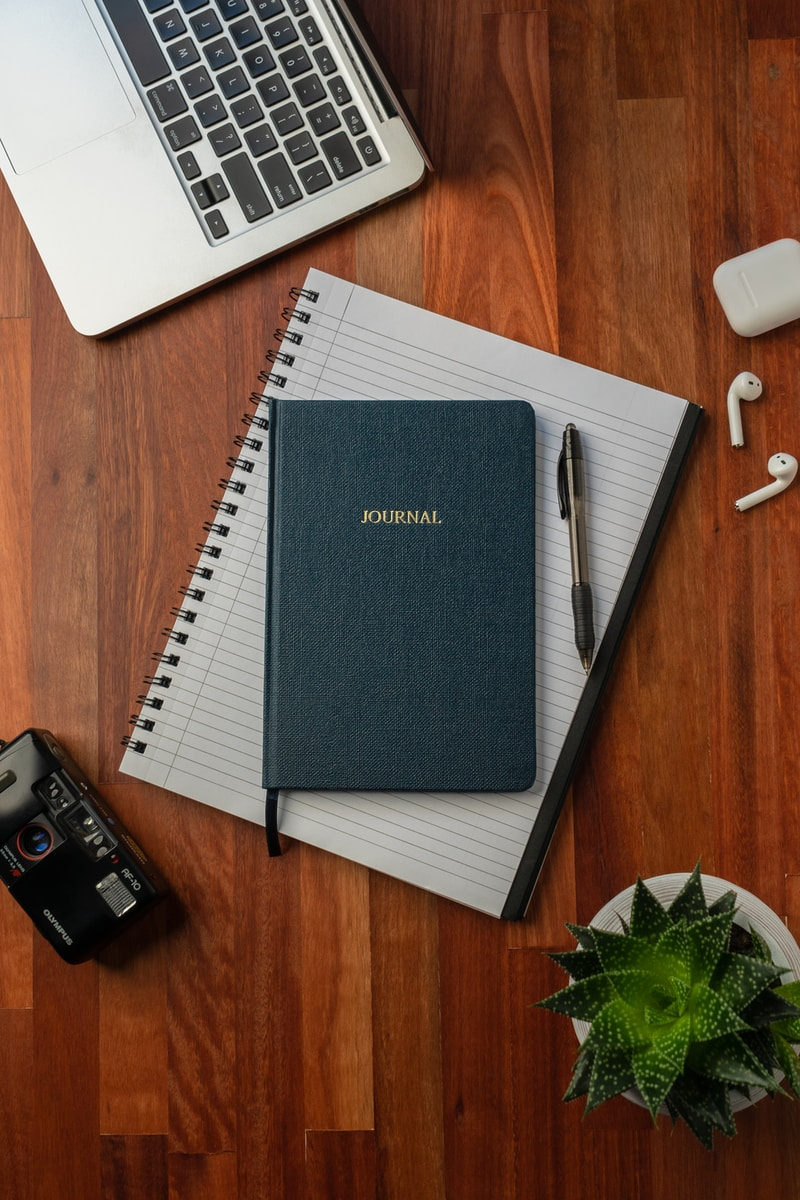 black spring notebook on brown wooden table